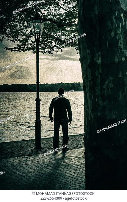 Silhouetted male figure standing by the lake