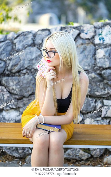 Young woman student on wooden bench waiting