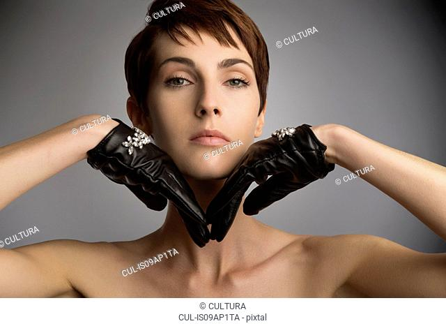 Studio portrait of woman with hands on chin wearing black leather gloves