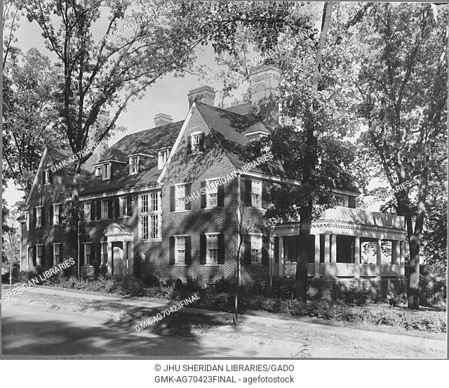 Photograph of a large Roland Park home made of brick, with two large balconies, a two-story home many windows, no front yard, the porch has two Doric columns