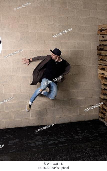 Young male street dancer dancing against wall