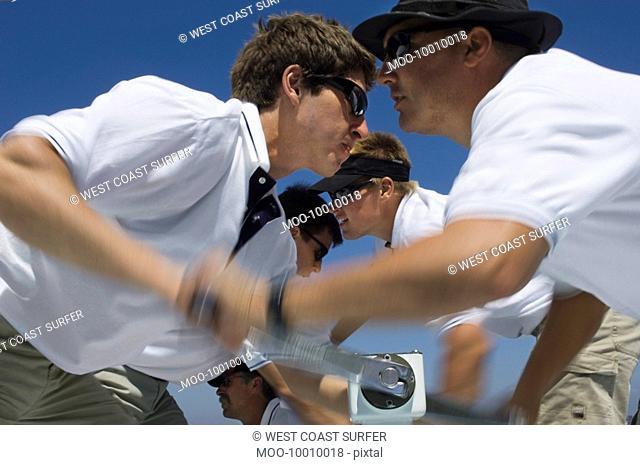 Sailors operating windlass on yacht side view