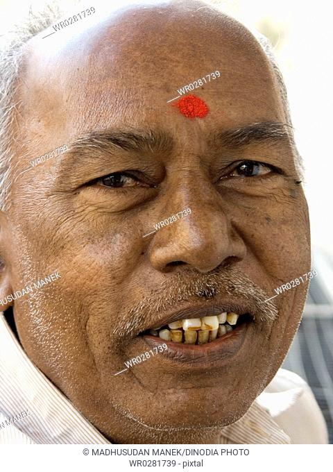 Old Indian man with red tilak on forehead looking at camera ,  684