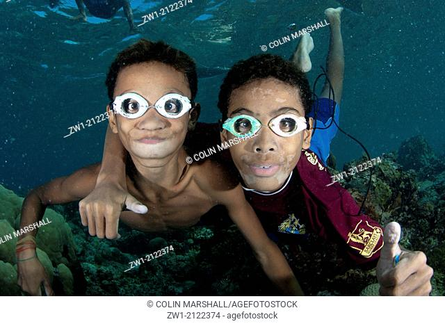 Pair of boys with goggles playing in the water at Pura Island near Alor in eastern Indonesia