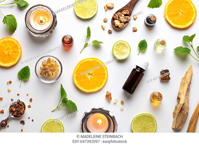 Bottles of essential oil with fresh citrus fruit, melissa, myrrh, white sandalwood and other ingredients