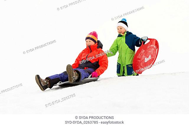 kids sliding on sleds down snow hill in winter
