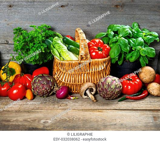 fresh herbs and vegetables on wooden background. raw food ingredients. country style picture. selective focus