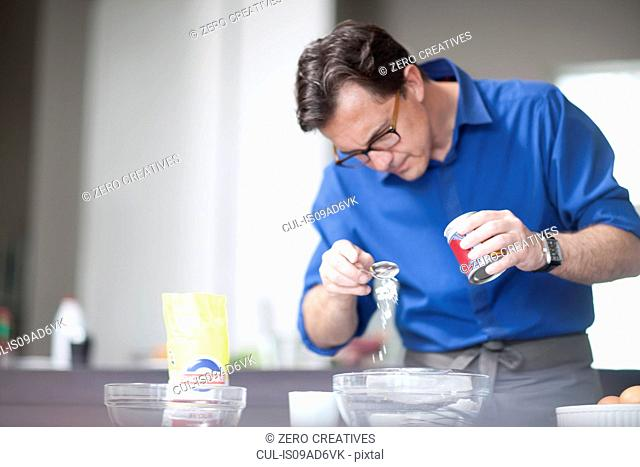Mature man adding spoonful of baking powder to mixing bowl