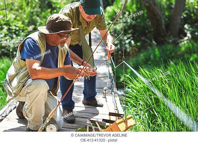 Active senior men friends preparing fishing line