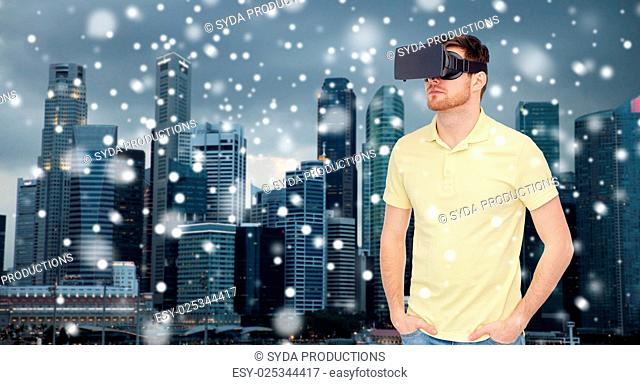 technology, augmented reality, travel, entertainment and people concept - young man with virtual headset or 3d glasses over singapore city skyscrapers...