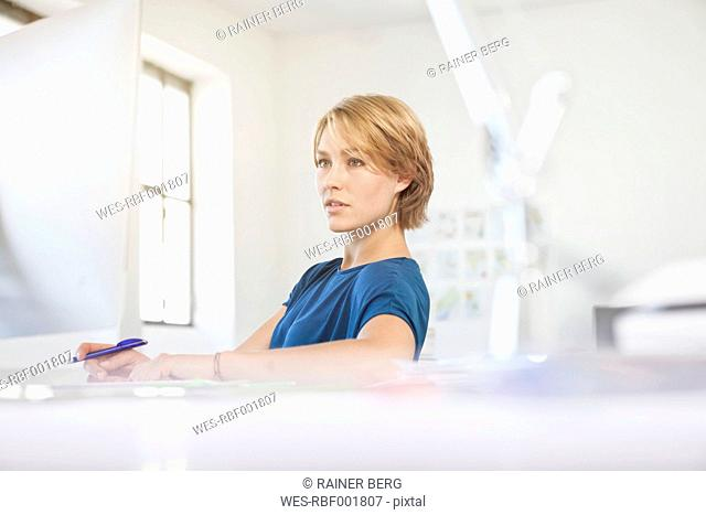 Portrait of young woman at her desk in a creative office