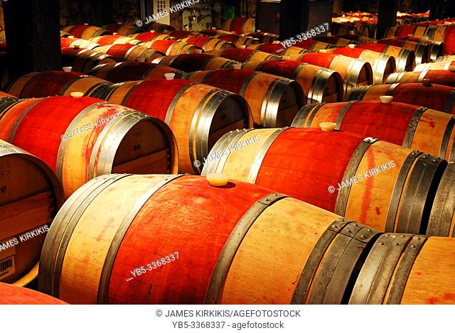 Wine ages in wooden barrels in a cellar in the Napa Valley