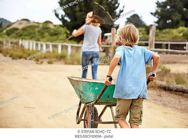 Boy with mother pushing wheelbarrow with horse dung