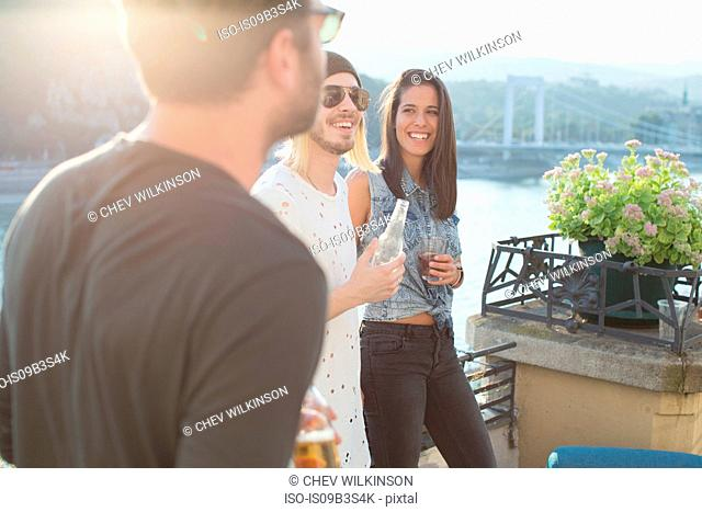 Three adult friends partying on waterfront roof terrace, Budapest, Hungary