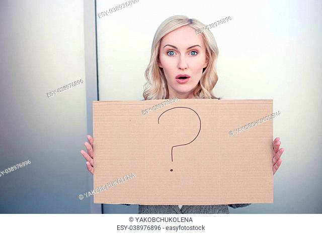 Beautiful young businesswoman is holding a signboard with a question mark on it. She is looking at the camera with frustration