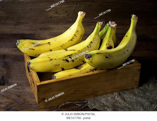 bananas in box on canvas and wooden board