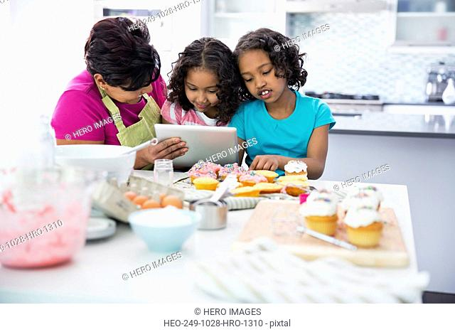 Grandmother and granddaughters searching for recipes on digital tablet