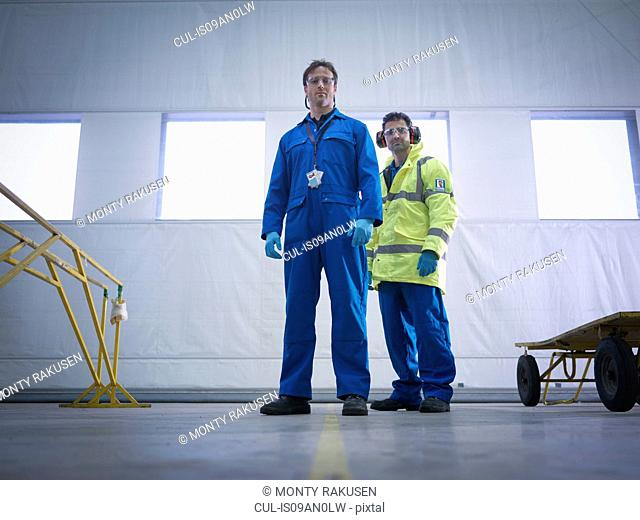Portrait of aircraft engineers in aircraft maintenance factory
