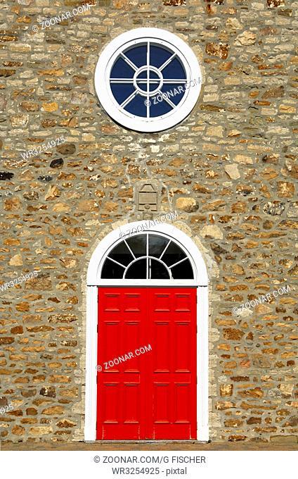 Rote Tür und weisse Rundfenster der Kirche Saint-Pierre-et-Saint-Paul, historisches Monument in der Ortschaft St-Pierre-de-l'Ile-d'Orleans auf der Insel Orléans...