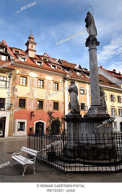 Pink frescoes on Old Town Hall building in the Town Square of Skofja Loka Slovenia with Mark of Mary ionic column monument