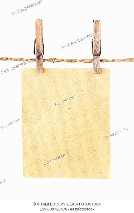 Piece old sheet of paper on two clothespins isolated on white background