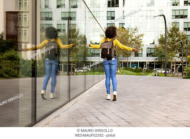 Back view of woman with backpack walking in the city