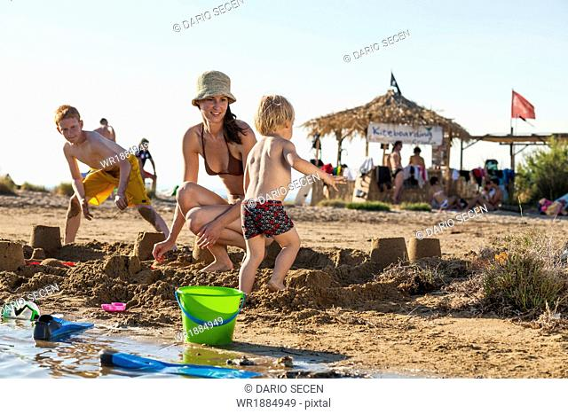 Croatia, Dalmatia, Mother With Sons On Beach, Background People