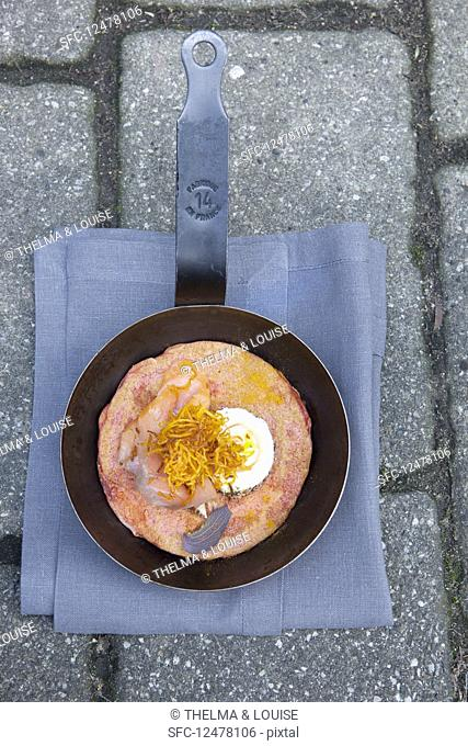 Blinis with turmeric, smoked salmon and goat's cheese in a pan