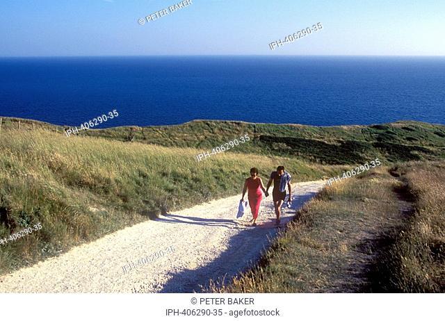Walkers on the coastal footpath above Man O'War Bay at Durdle Door on Dorset's Jurassic Coast near Lulworth Cove