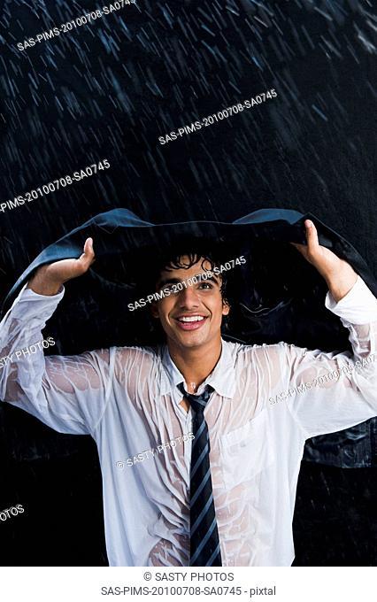 Businessman enjoying in the rain