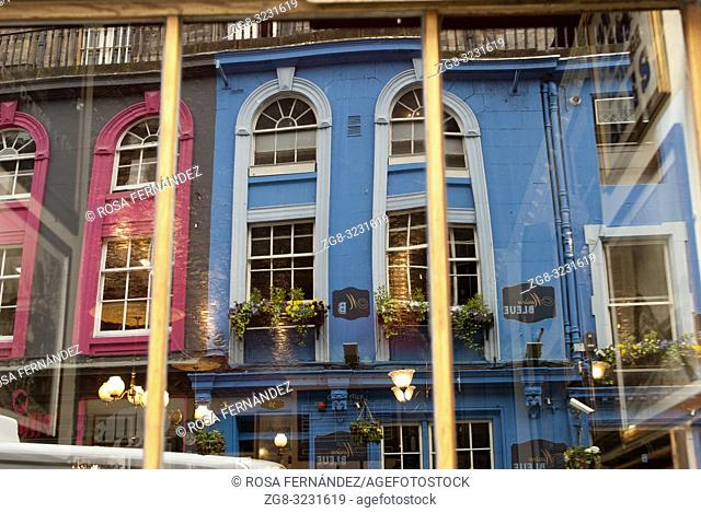 Colored facades in blue and pink reflected on a window shop at Victoria Street, Old Town, Edinburgh, Scotland, United Kingdom