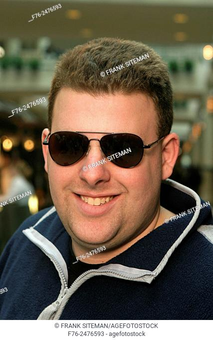 Portrait of an adult wearing sunglasses and smiling in a generic indoor environment