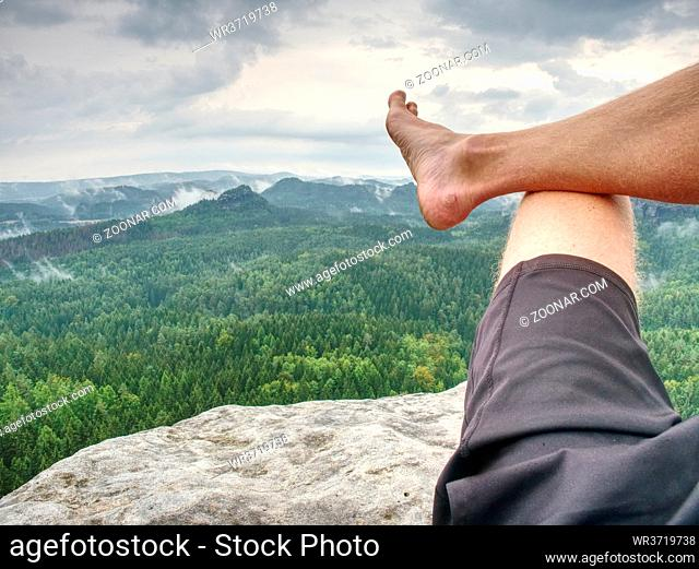 Man taking a break in nature and looking from summit down at the distant landscape