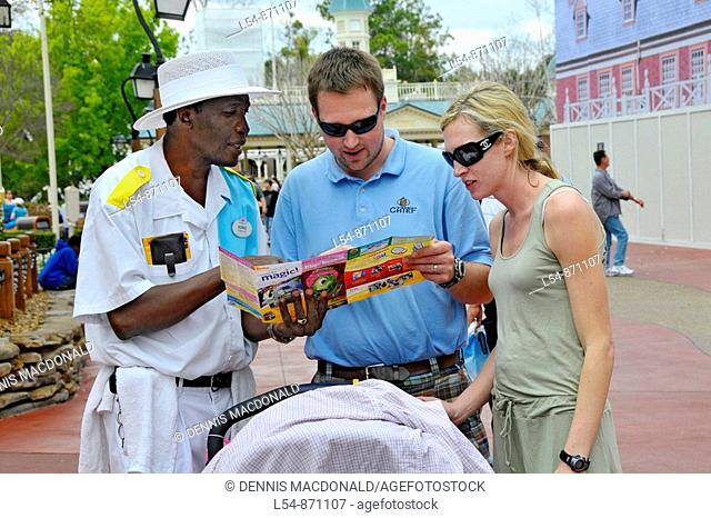 African American male guide helps White young couple with child and stroller look at map at Walt Disney Magic Kingdom Theme Park Orlando Florida Central