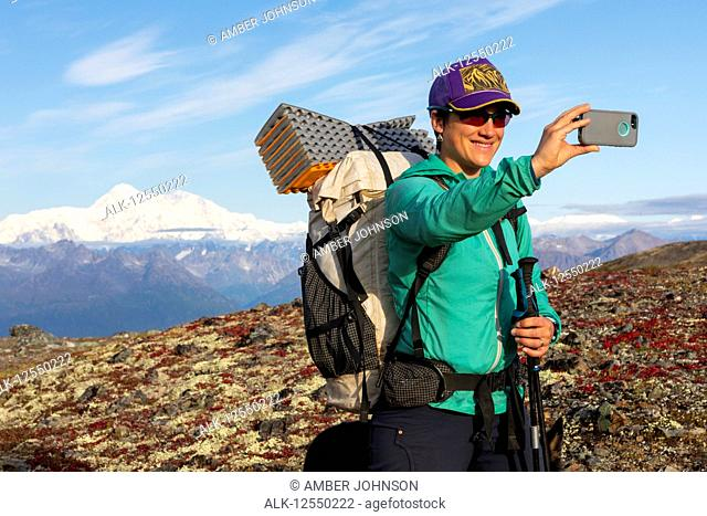 Woman taking selfie while backpacking with Denali in the background, along the Kesugi Ridge Trail, Denali State Park on a sunny autumn day, Southcentral Alaska