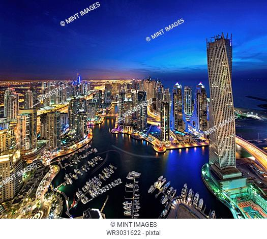 Aerial view of the cityscape of Dubai, United Arab Emirates at dusk, with illuminated skyscrapers and the marina in the foreground
