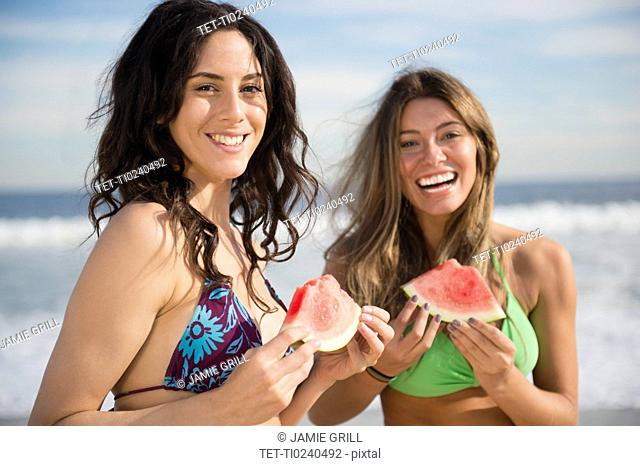Two women eating watermelon at beach
