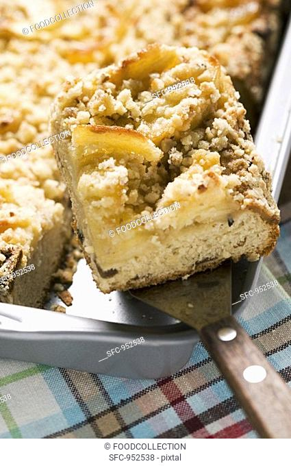 Apple crumble cake in baking tin with piece on server