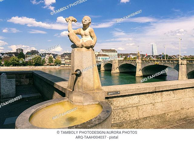Fountain with statue of little boy holding fish at mittlere bridge in summer, Basel, Switzerland