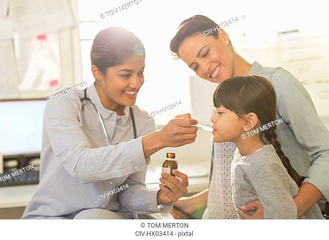 Female pediatrician feeding cough syrup to girl patient in examination room