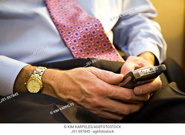 TEXAS  Austin   Male executive enter text using keypad on cellular telephone while working in hotel room, left handed, watch