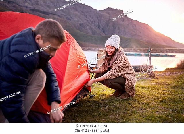 Young couple pitching tent at lakeside campsite