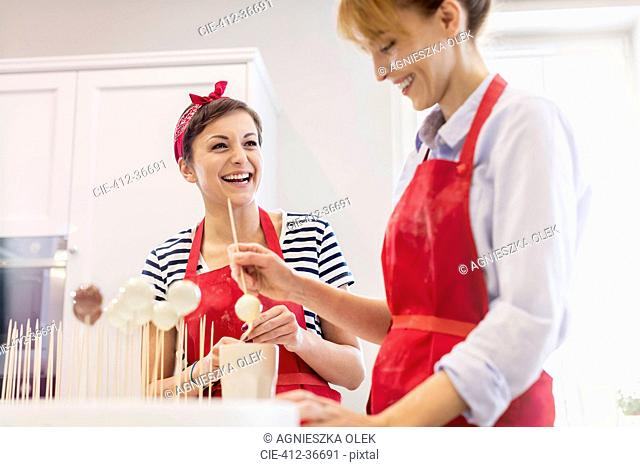 Smiling female caterers baking, making cupcake pops in kitchen