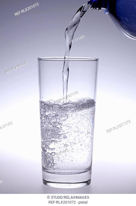 Mineral water pouring into glass