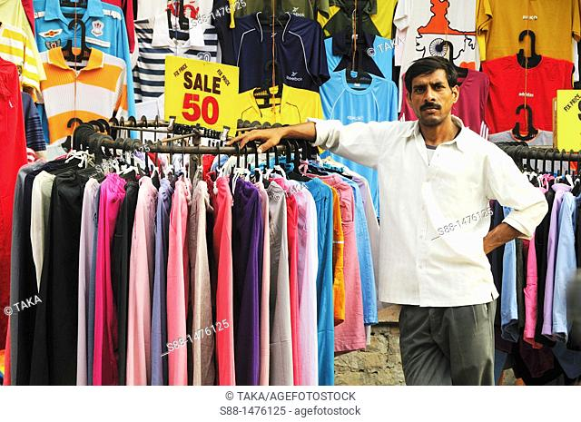 Man sells clothes on the main shopping street, New Delhi, India