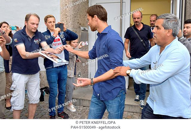 Real Madrid player Xabi Alonso (C) leaves the office of a sports doctor after a check-up and signs autographs in Munich, Germany, 28 August 2014
