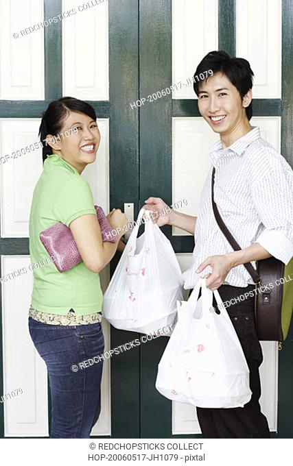 Portrait of a young couple standing in front of a door and holding plastic bags