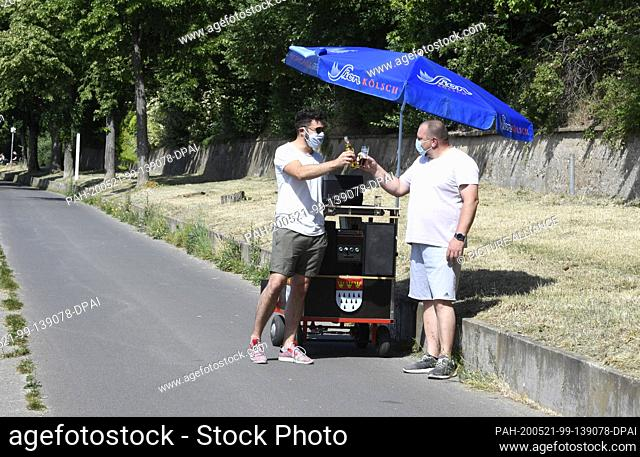 21 May 2020, North Rhine-Westphalia, Cologne: Two friends celebrate Father's Day with their Bollertag and beer. Traditionally the men walk through the streets...