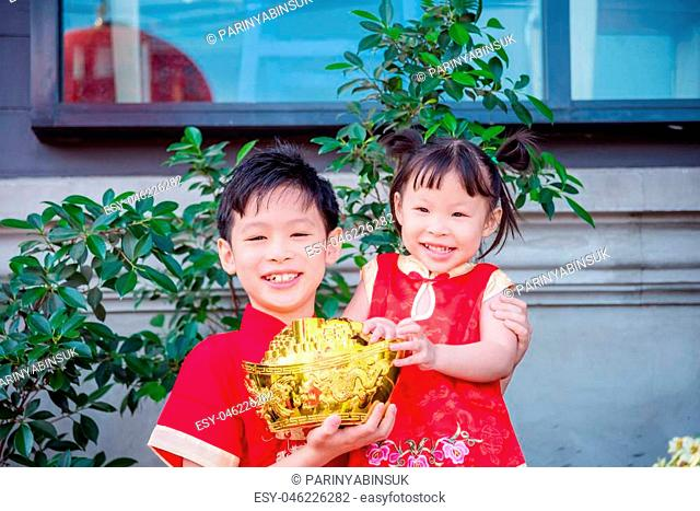 boy and girl wearing traditional dress and holding golden money bank with smile
