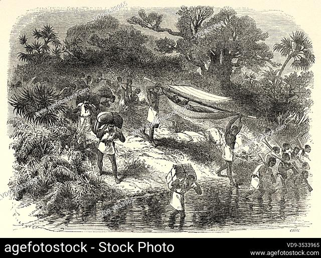 Porters crossing a river on the route to Dahomey, Central Africa, Old 19th century engraved illustration, Le Tour du Monde 1863